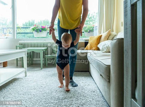 mother assisting toddler with his first step indoors