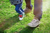 First steps concept - foot of father and son in stylish sneakers on the background of green grass. Baby learning to walk and making his first steps holding the hands of his father. Copy space.