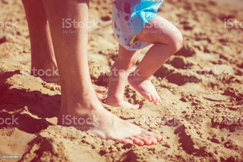 First steps of a baby on the beach stock photo
