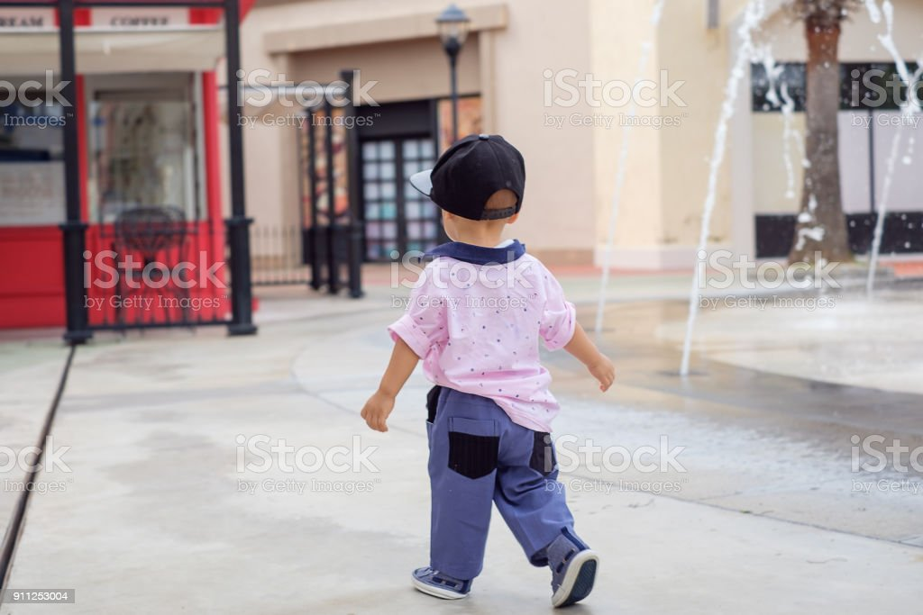 First steps of  Baby boy child near water fountain at park stock photo