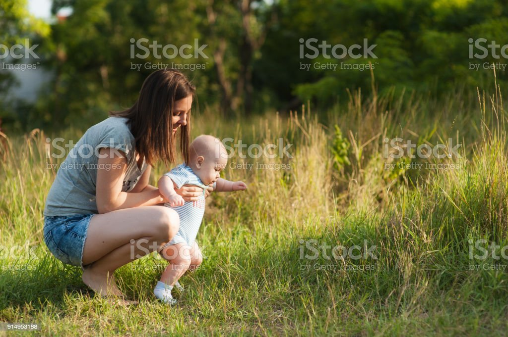 First steps. Young beautiful woman in green grass background learning cute child baby boy to walk on nature. Mother, little kid son. Parenthood, family day 15 of may, love, parents, children concept. stock photo
