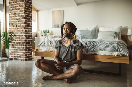 Young men practicing yoga at home. He is in bedroom and doing yoga, first thing in the morning.