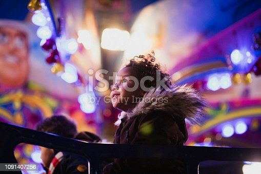 A close-up shot of a little girl's first time at the funfair​, she is looking at all of the decorations in awe.