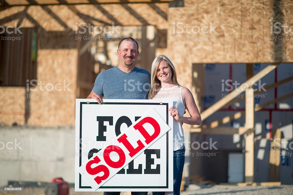 A husband and wife are standing with a for sale sigh in front of...