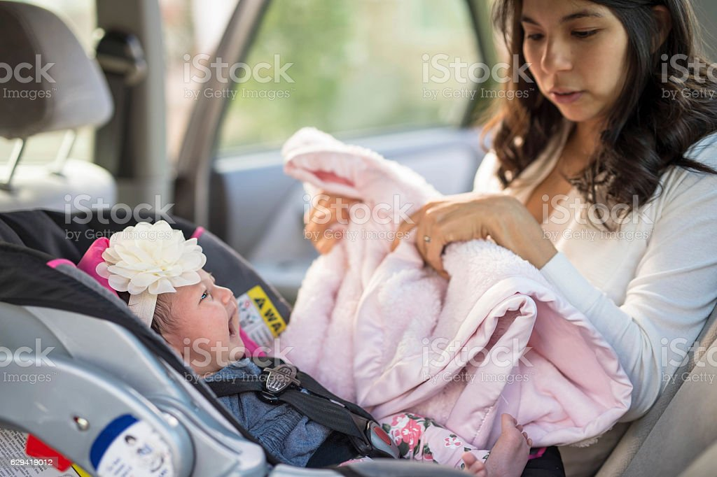 First time mother struggling to put baby in carseat stock photo