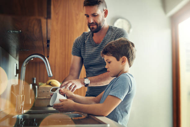 First we eat together then we clean together Shot of a father and son washing dishes together at home chores stock pictures, royalty-free photos & images