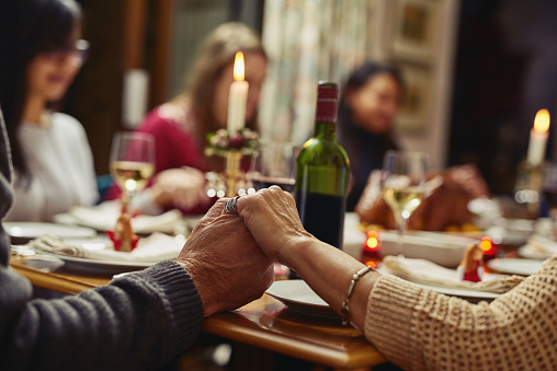 Closeup shot of people holding hands in prayer before having a meal together