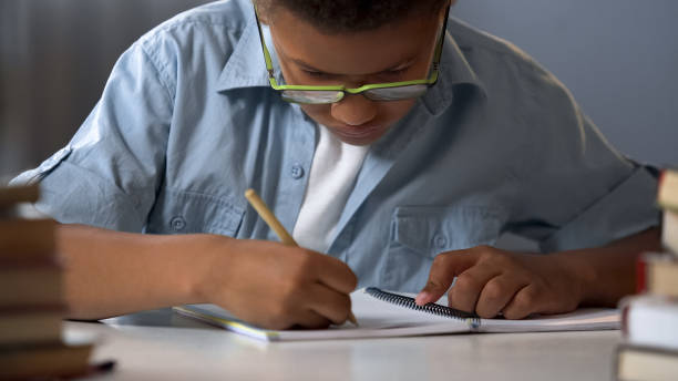 First-grader boy carefully writing letters in his copybook, doing homework stock photo