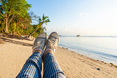 First-person view, a girl swinging on a swing on a sandy beach of a tropical island at sunset. Enjoys the vacation