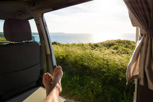 visão em primeira pessoa de um homem descalço relaxando dentro de uma van de campista e apreciando a vista sobre o mar ao pôr do sol através da porta de correr aberta com gramíneas selvagens em primeiro plano. - escapismo - fotografias e filmes do acervo
