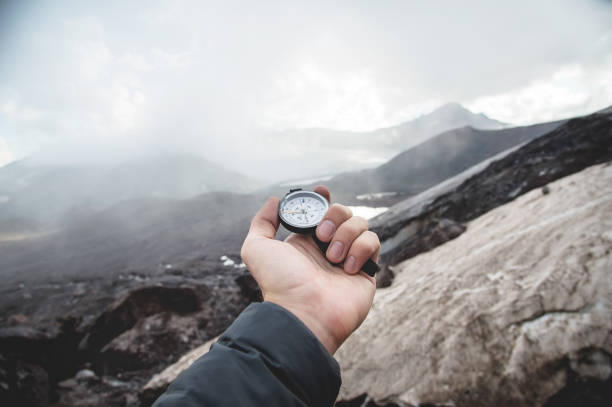 A first-person view of a man's hand holding a magnetic compass against of Caucasus mountains stock photo