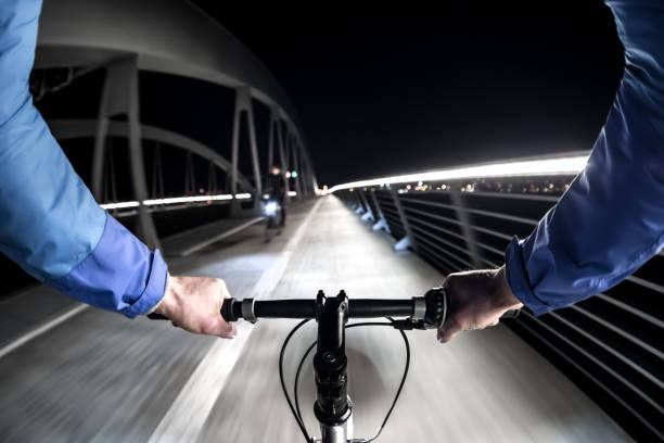 first-person-ansicht der radfahrer in der stadt bei nacht - radwege deutschland stock-fotos und bilder