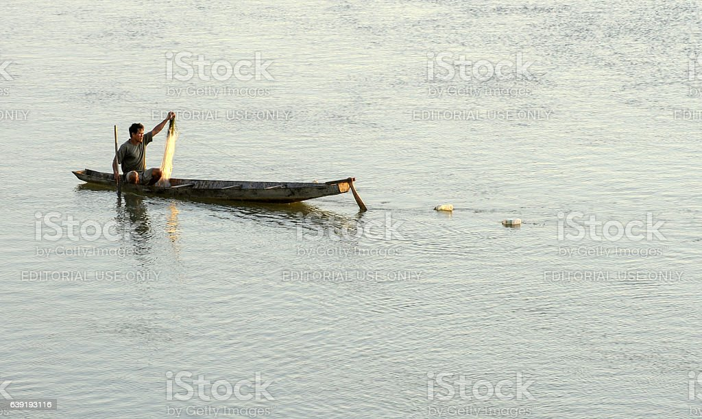 fiserman on his canoe retreating the fishing stock photo