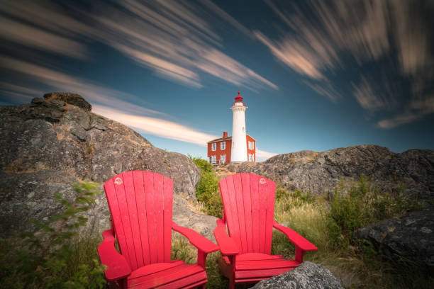 Fisgard Lighthouse and red chairs long exposure stock photo