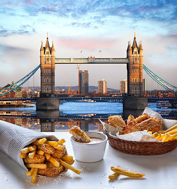 fish and chips vor der tower bridge in london, england - kartoffelturm stock-fotos und bilder