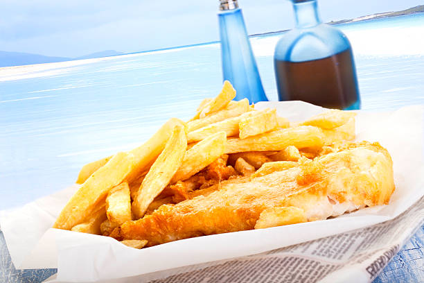 fish and chips by the sea - newspaper beach stockfoto's en -beelden