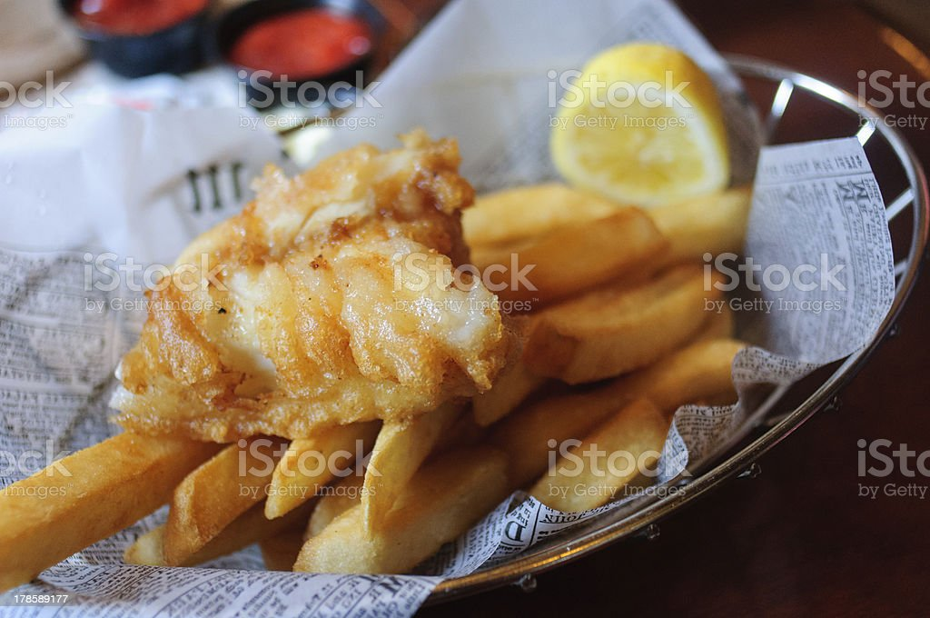 Fish and chips in a basket with a lemon stock photo