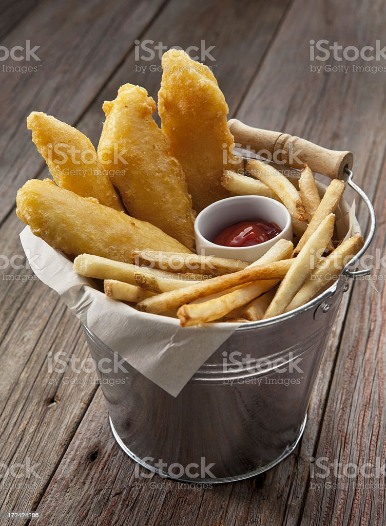 Fish and Chips In A Metal Bucket on Rustic Background. stock photo