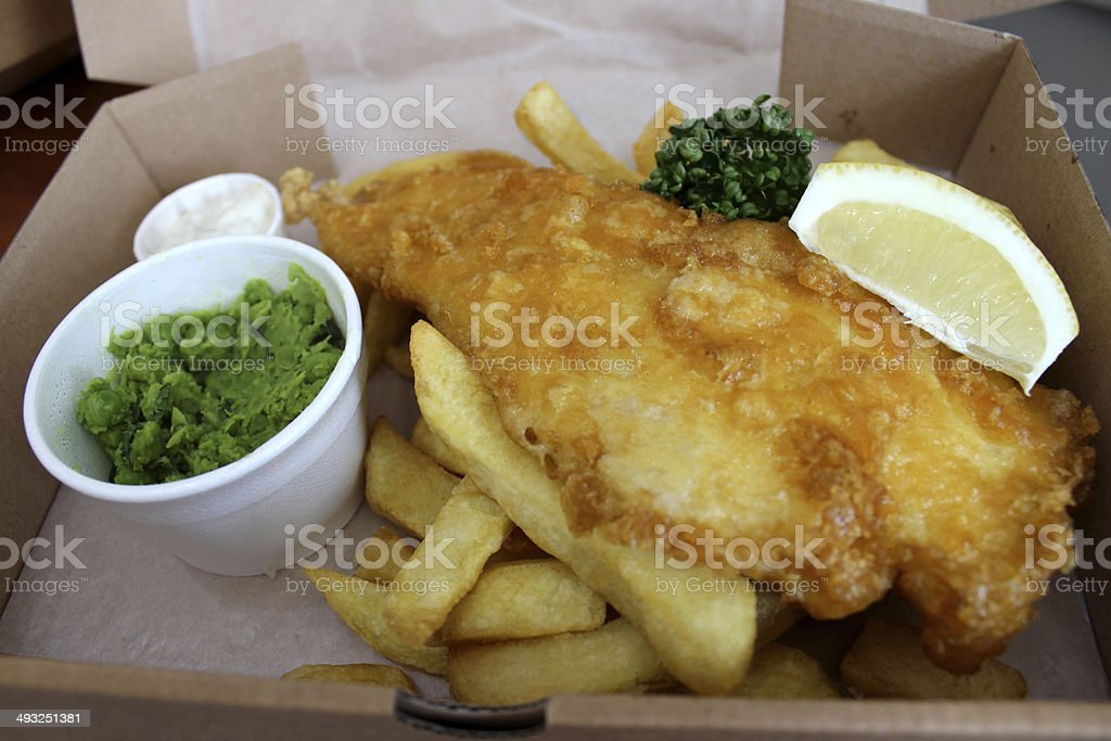 Fish and chips (cod) in box with peas, tartar sauce stock photo