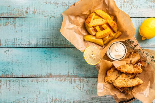 peixes e microplaquetas na tabela de madeira azul, alimento tradicional britânico. - frito - fotografias e filmes do acervo