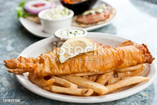 Close up picture of a plate containing fried fish and chips