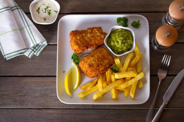 Pescado y patatas fritas servidos con limón, guisantes y salsa. - foto de stock