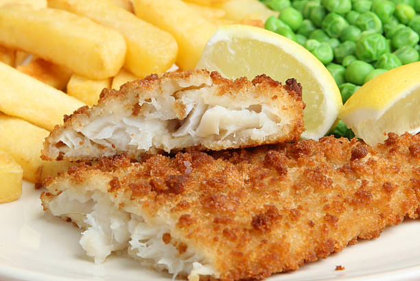 Fish and chips with lemon and petit pois Breaded cod fillet with chips and peas fritter stock pictures, royalty-free photos & images