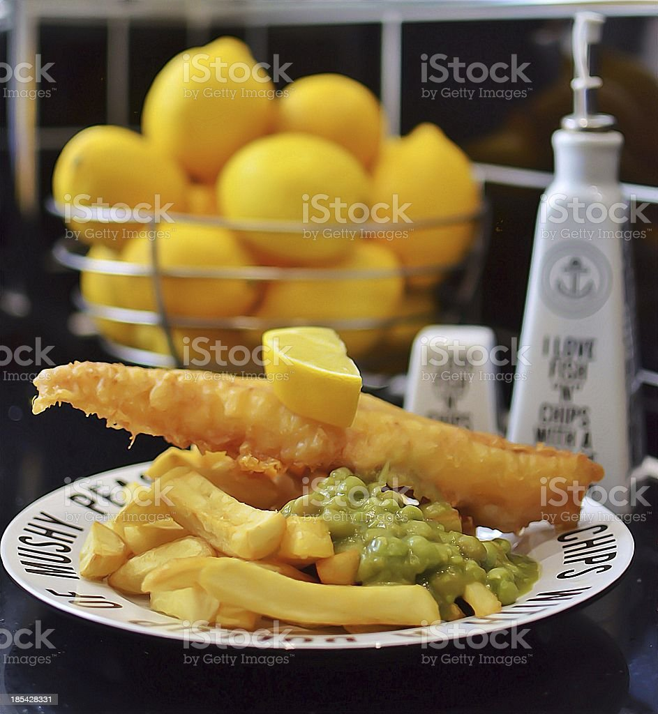 Fish and chips with peas , salt, vinegar, lemons royalty-free stock photo