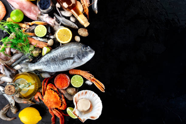 Fish and seafood background with copy space, a flat lay top shot. Sea bream, crab, squid, scallops on black with a place for text stock photo