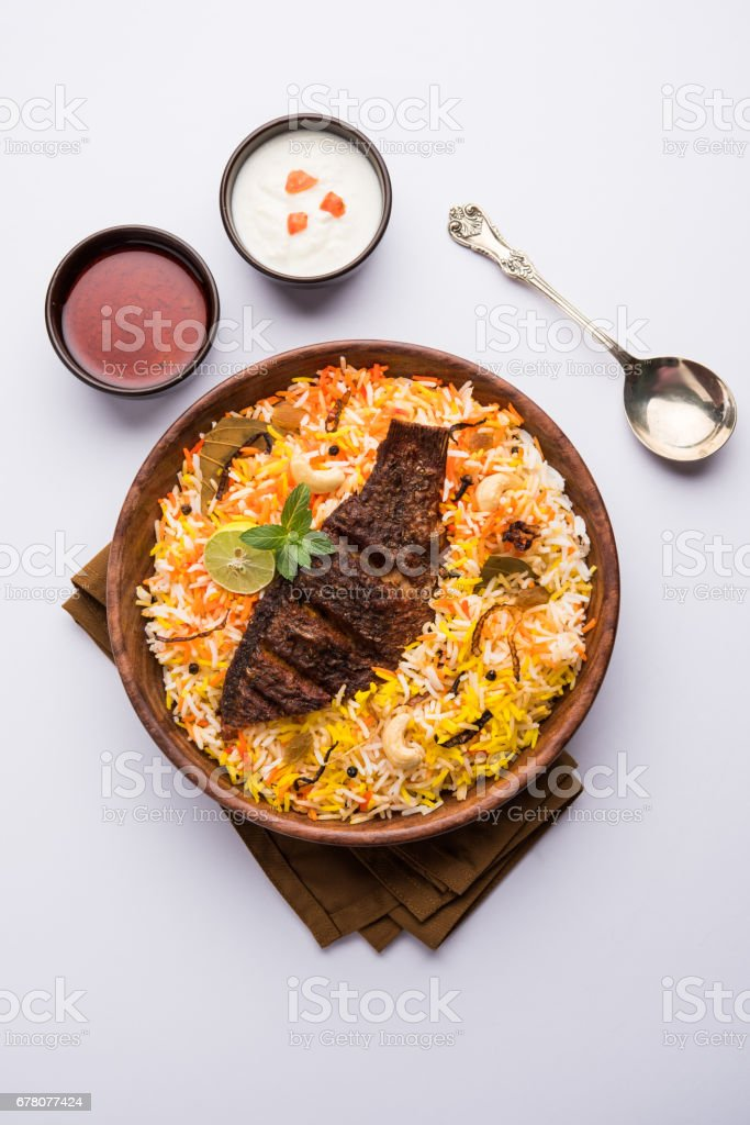 Fish Biryani or fish Rice - Popular Indian non-vegetarian recipe made of fish marinated with Indian spices fresh herbs and cooked with Basmati rice, selective focus stock photo
