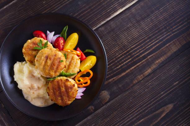 Pasteles de pescado con puré de patatas y verduras. Empanadas de pescado. Chuletas fritas de pescado picado - foto de stock