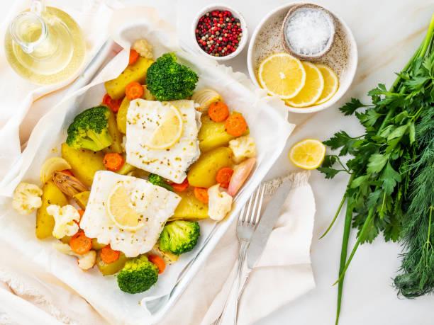 fische kabeljau gebacken im ofen mit gemüse - gesunde ernährung gesunde ernährung. leichte weiße marmortisch, textfreiraum, ansicht von oben - gebackener blumenkohl stock-fotos und bilder