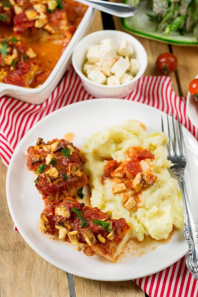 fish cod baked in tomato sauce with feta cheese - ofengemüse mit feta stock-fotos und bilder
