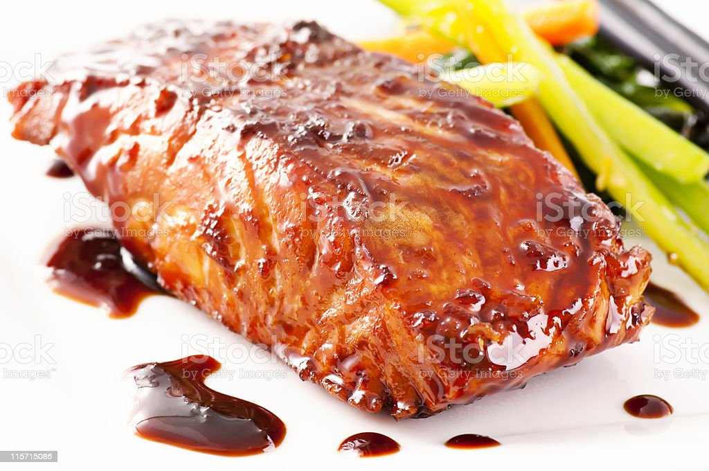 Fish cooked in teriyaki sauce with vegetables on the side stock photo