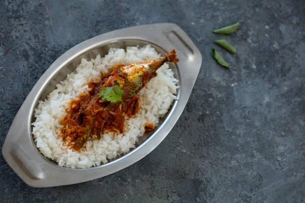 fish curry, indian dish, indoor lighting stock photo