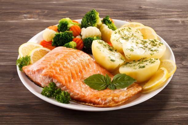 fischgericht - gebratener lachs mit gemüse - salzkartoffel stock-fotos und bilder