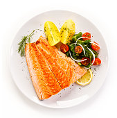 Fish dish - grilled salmon and vegetables on white background