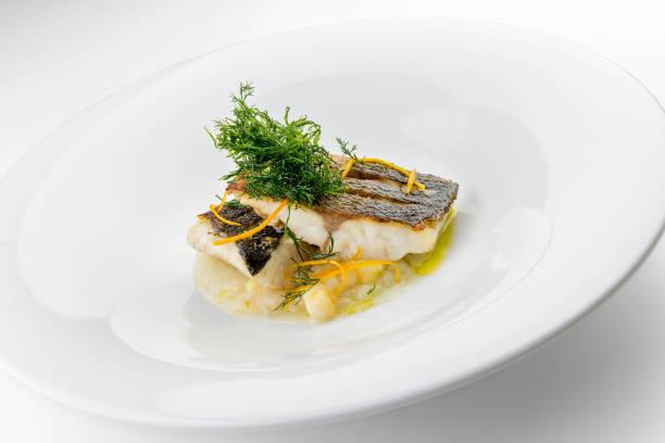 pescado plato rebanadas de filetes de lubina sobre puré verduras - rodaballo fotografías e imágenes de stock