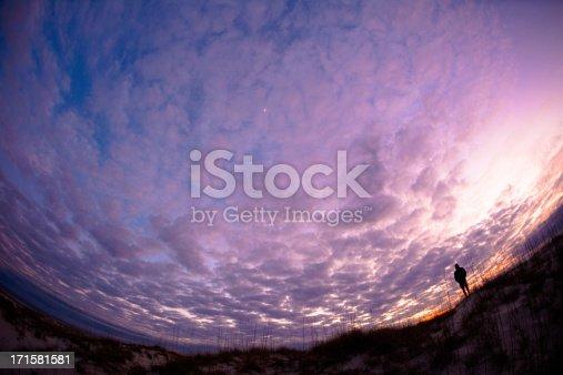 Fish Eye perspective of man standing on coastal shoreline at sunset