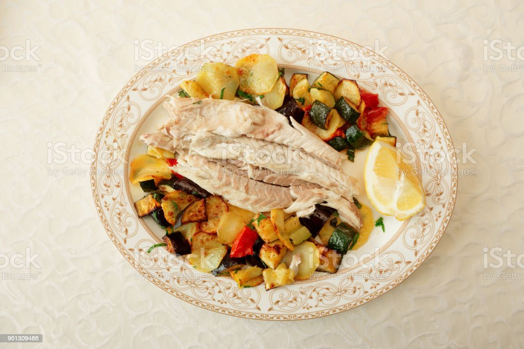 Fish fillet baked with vegetables on table in a restaurant stock photo