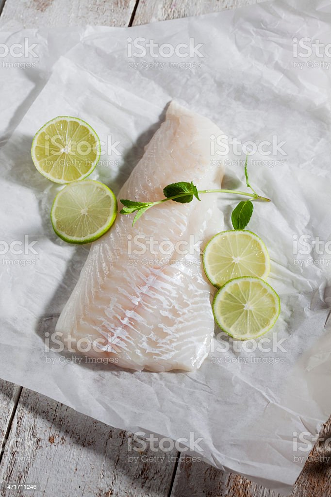 Fish fillet, haddock, limes and herbs on greaseproof paper stock photo