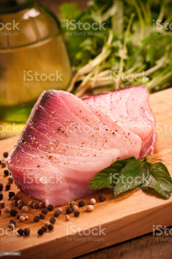 Fish fillet on wooden board with garnish stock photo