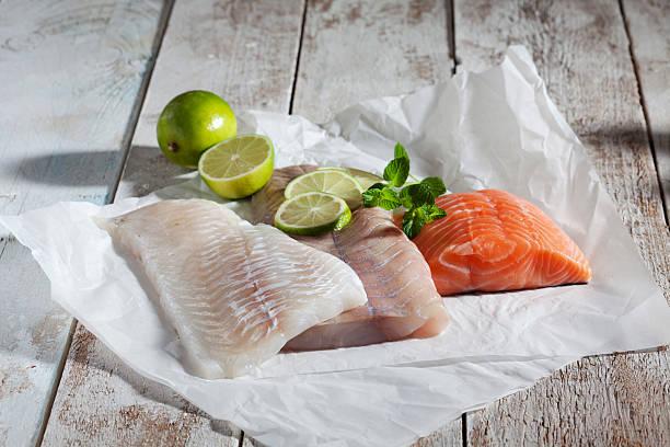 Fish fillets, haddock, coalfish, salmon, limes, herbs, greaseproof paper stock photo
