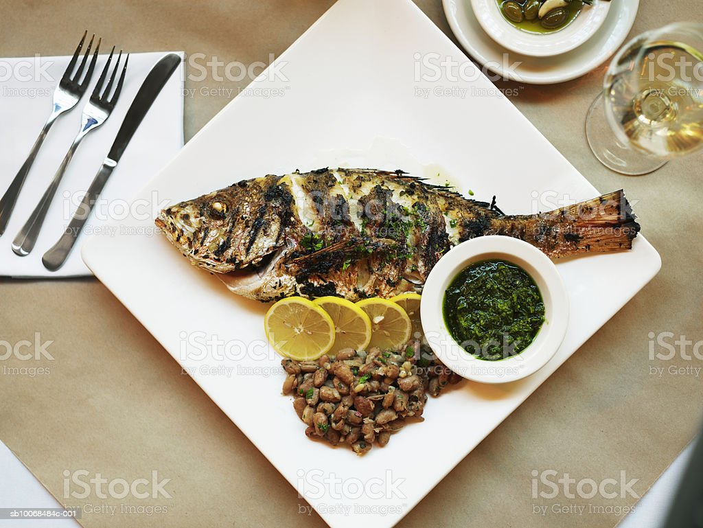 Fish grilled with salsa verde and cranberry beans, close-up royalty-free stock photo