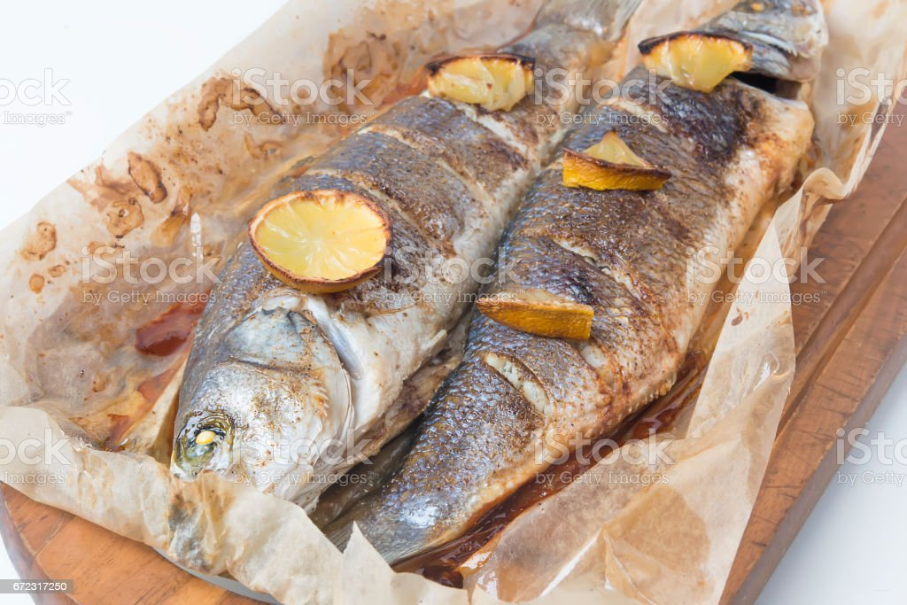 fish, grouper with a lemon and vegetables prepared on a grill(European seabass, branzino fish) stock photo