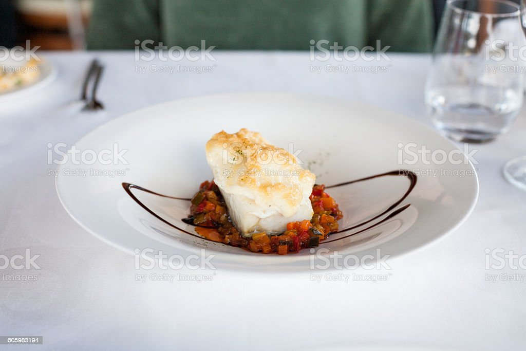 fish hake cooked with vegetables in white dish stock photo