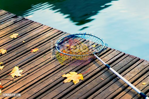 istock Fish landing net for fish, fishing tackle on a wooden bridge with fallen autumn yellow maple leaves. Minimalistic autumn background 1068518128