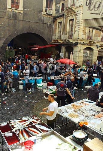 Catania, Italy - 2nd November 2018: Fishmongers selling and people buying seafood at the pubic fish market of Catania