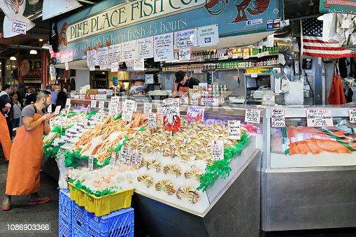 Seattle, USA - September 19, 2018: iconic fish vendors at the Pike Place Market - one of the oldest public farmers markets in the United States (opened 1907). It is Seattle's most popular tourist attractions. It houses the businesses for many farmers, fishmongers, craftspeople and merchants who operate in its covered arcades.