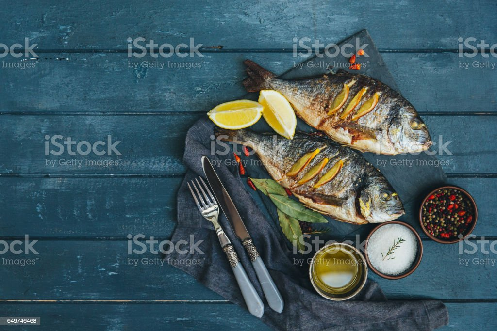 Fish Meat on a Black Tray with Herbs and Spices on Top of a Rustic Wooden Table stock photo